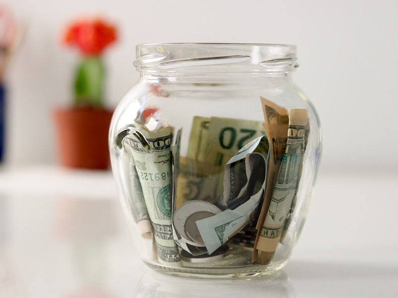 Money tucked into a clear jar