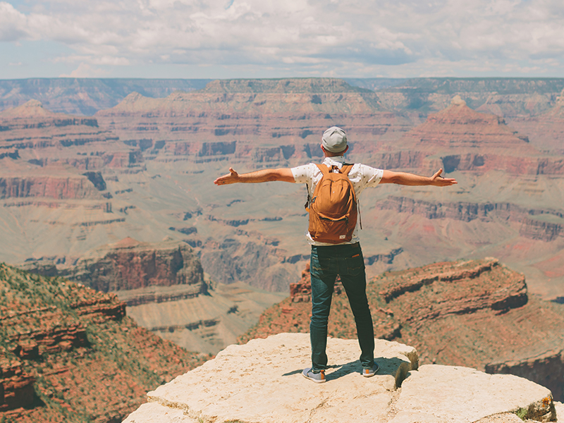 A person wearing an orange backpack stands at the rim of the Grand Canyon with arms spread.