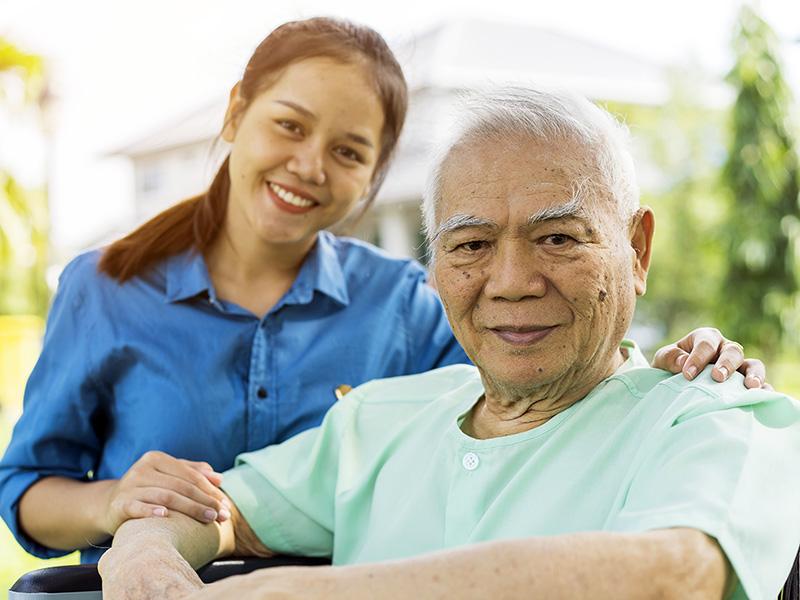 Smiling woman kneels next to smiling older man in wheelchair.
