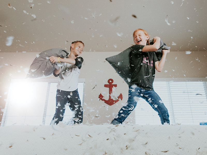 Two children jumping on a bed having a pillow fight