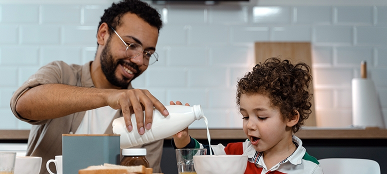 A man and his son eat breakfast at a kitchen table