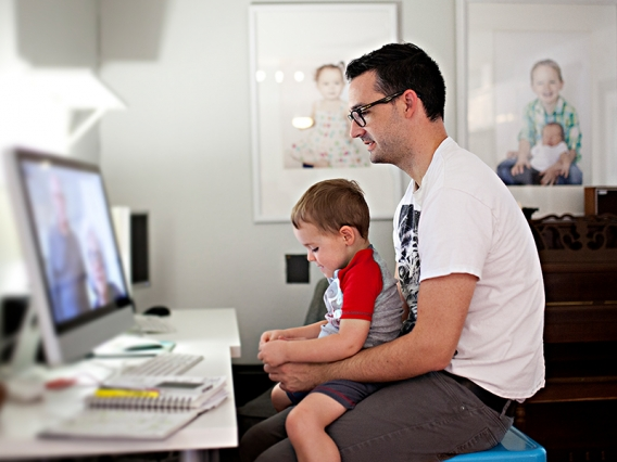 Man at computer with toddler in lap video chats with grandparents