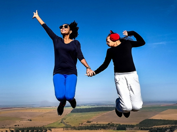 Two women jumping in the air with a blue sky behind them