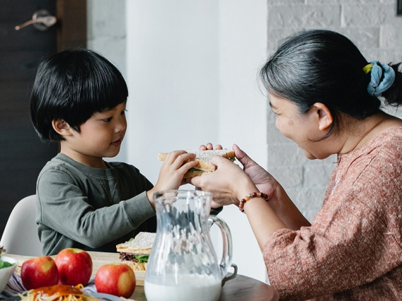 An older woman offers a sandwich to a young child