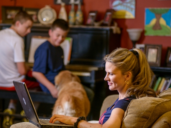 A woman looks at a laptop with children in the background